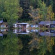 House and autumn forest on the lake — Stock Photo #50203603