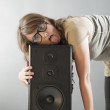 Beautiful woman laying on the big wooden speaker — Stock Photo