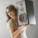 Beautiful woman holding big wooden speaker — Stock Photo #16307655