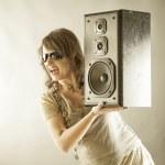 Beautiful woman holding big wooden speaker — Stock Photo #16307673