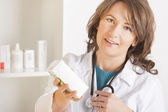 Young woman pharmacist or doctor with a bottle of drugs — Stock Photo