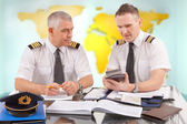 Airline pilots filling in papers in ARO — Stock Photo