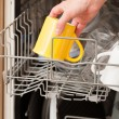Hand putting a mug into a dishwasher — Stock Photo #28801039