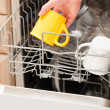 Hand putting a mug into a dishwasher — Stock Photo