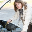 Woman checking oil level — Stock Photo #34393301