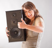 Beautiful woman holding big wooden speaker — Stock Photo