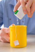 Sweetener tablets and hand with box whit cup of tea — Stock Photo