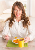Woman eating breakfast at home — Stock Photo