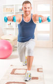 Handsome man doing exercises at home — Stock Photo