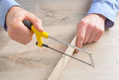 Cutting plastic molding with handsaw — Stock Photo