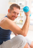 Handsome man holding dumb bells — Stock Photo