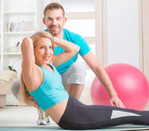Woman with personal trainer at home — Stock Photo
