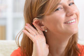 Woman wearing deaf aid — Stockfoto