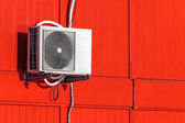 Airconditioning unit on red wall — Stock Photo