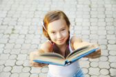Girl holds out a book — Stock Photo