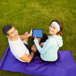 Sports couple using digital tablet — Stock Photo #39451875