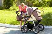 Young mother with a stroller — Stock Photo