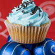 One blue cupcake and two christmas balls — Stock Photo