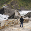 Stone bridge in San Juan de Gaztelugatxe with a woman — Stock Photo