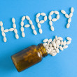 Word happy written whith pills on blue background — Stock Photo
