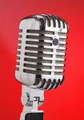 Mikrofon metall röd bakgrund. — Stockfoto
