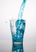 Blue water pouring into a glass — Stock Photo