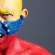 Man face painted with venezuelan flag, angry expression. — Stock Photo #26356641