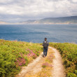 Stock Photo: Womwalking along path on coast