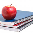 Three notebooks and red apple — Stock Photo