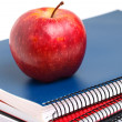 Three notebooks and red apple in vertical composition — Stock Photo