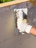 Man spreading tile adhesive with a trowel — Stock Photo