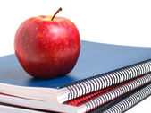 Three notebooks and a red apple — Stock Photo