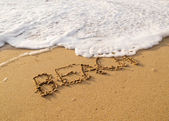 Word beach written in the sand on the beach — Stock Photo