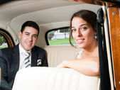 Bride and groom in a classic car — Stock Photo