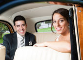Bride and groom inside a beautiful classic car — Stock Photo