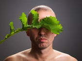 Man with a stalk of vegetable concealing his identity — Stock Photo