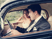Bride and groom inside a classic car, vintage tone — Stock Photo
