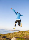 Man giving a big jump while practicing trail running — Stockfoto