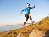 Man practicing trail running in a coastal landscape — Stock Photo