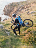 Cyclist carrying your bike on the Galician coast. — Stock Photo