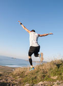 Man practicing trail running with a coastal landscape — 图库照片