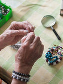 Hands of senior woman making a necklace — Stock Photo