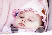 Baby flicka sover i vagnen. — Stockfoto