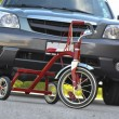 Stock Photo: Child's Tricycle in front of SUV