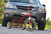 Child's Tricycle in front of SUV — Stock Photo