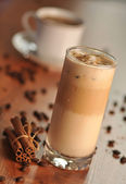 Cold fresh ice coffee with coffee beans and cinnamon - close up — Stock Photo