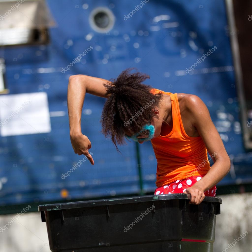 AURILLAC, FRANCE - AUGUST 23: A dancer is standing in a trash can as part of the Aurillac International Street Theater Festival,show by the Company Empreintes, on august 23, 2012, in Aurillac,France.  — Stock Photo #13875282