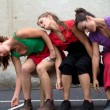 Three dancers are slanting on a bench - Stock Photo