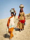 Two Indian women carrying water in the desert. — Stock Photo