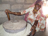 Bishnoi woman turning a millstone. — Stock Photo